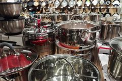 Set of new metal pots kitchen cookware in a shop. Set of new metal pots cookware in a shop royalty free stock images