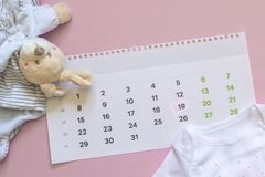 Set of newborn accessories in anticipation of  child - calendar with circled number 19 nineteen, baby clothes, toys on pink. Background. Copy space, flat lay royalty free stock image