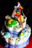 Set of newborn baby things - cake made from diapers on dark background stock photos
