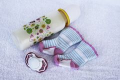 Set for newborn girl with baby milk, toy and mittens. Set for newborn girl with baby milk, toy, pacifier, anti scratch hand guard mittens and socks on white Stock Images