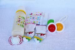 Set for newborn girl with baby milk, toy, pacifier, mittens and Royalty Free Stock Photos