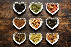 Set of nine assorted raw tea bowls shaped as hearts. Set of nine assorted sorts of raw tea in tiny bowls shaped as hearts on weathered wooden surface Stock Images