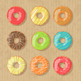 Set of nine bright tasty vector donuts illustration on the cardboard box background. Doughnut icon in cartoon style Royalty Free Stock Image