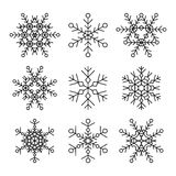 Set of nine vector simple linear snowflakes icons. Hipster black and white design elements. Stock Image