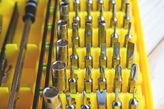 A set of nozzles of different sizes for screwdriver close-up in a yellow box, daddy`s Toolbox. A set of nozzles of different sizes for screwdriver close-up in a Royalty Free Stock Images