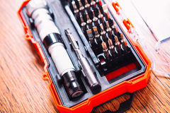 Set of nozzles for screwdriver in red box on wooden background Royalty Free Stock Photography