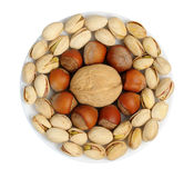 Set of nuts on a white plate, isolation Royalty Free Stock Images