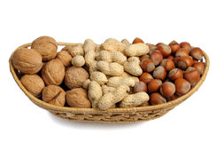 Set of nuts in a wicker basket, isolated Royalty Free Stock Photos