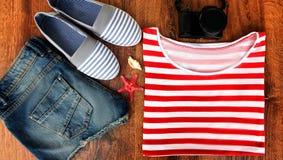 Set odziewa dla iść morze: cajgów skróty, pasiasta koszula i sneakers, photocamera, skorupy, odgórny widok drewniany Zdjęcia Stock