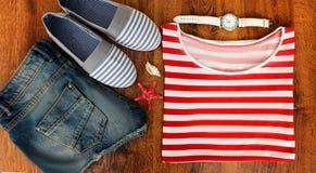 Set odziewa dla iść morze: cajgów skróty, pasiasta koszula i sneakers, zegarki, skorupy, odgórny widok drewniany Zdjęcie Stock