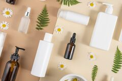 Free Set Of Care Cosmetics. Various Bottles, Tubes With Cosmetic, Chamomile Flowers, Fern Leaves On A Beige And Brown Background. Stock Image - 191759381