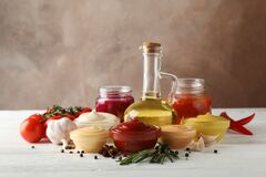 Free Set Of Different Delicious Sauces, Garlic, Cherry Tomatoes, Olive Oil On Background, Space For Text Royalty Free Stock Photo - 169509825