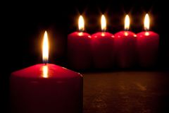 Set Of Red Candles Burning In The Dark Stock Photo