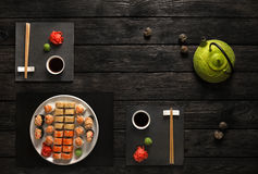 Free Set Of Sushi And Rolls With Teapot On Black Rustic Wood, Top View Royalty Free Stock Photography - 86165527