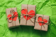 Free Set Of Three Gift Boxes Tied With A Rope On Green Crumbled Paper Background. Carton Hearts Cards. Stock Images - 153998974