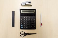 A set of office tools consisting of a calculator, pen, stapler, stock photo