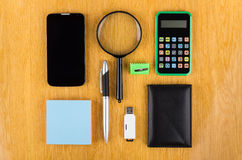 Set of office tools, modern smartphone and flashcard. On wooden table Royalty Free Stock Image