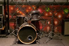 A set of old beat-up dusty drums, on a stage stock photo