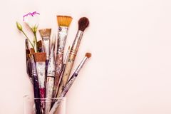 Set of old brushes, flower and palette knife on pale pink background.  stock photography