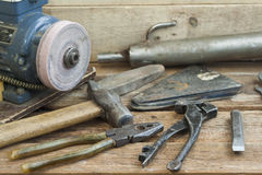 Set of old hand tools lying on a wooden bench. In the background of the winepress, with an electric motor and an old pipe. Stock Images