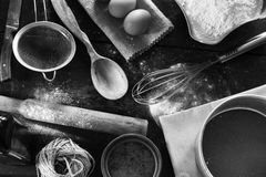 A set of old kitchen items. Black and white photo. A set of old kitchen items close-up view from above. Kitchen table in a rustic style. Products for baking stock image