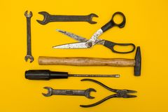 Set of old rusty tools on a yellow background, with space for text royalty free stock photography