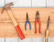 Set of old tools hammer, pliers and soldering Iron on wooden b royalty free stock photo