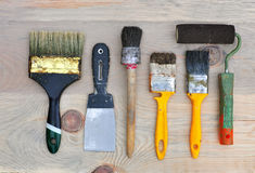 Set of old tools to repair and paint. Set of old tools to repair and paint on a wooden surface: brush, spatula, roller. Top view Stock Photo