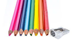 Set of old used broken colour pencils and metal sharpener. Royalty Free Stock Image