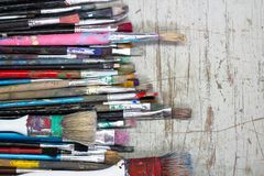 Set of old worn out paint brushes. Set of old worn out paint brush dirty with paint on a old wooden board as artistic vintage equipment and creativity background Royalty Free Stock Image