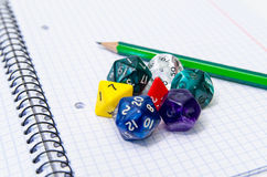 Set of open exercise book, pencil and dices Stock Photo