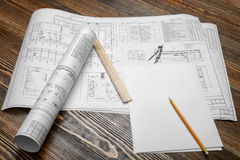 A set of open and rolled up blueprints on wooden table background with a pencil, a ruler and compasses lying beside. Stock Photos