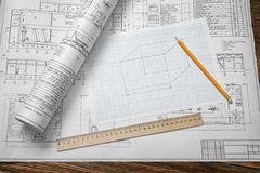 A set of open and rolled up blueprints on wooden table background with a pencil and a ruler lying beside. Stock Image