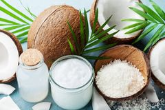Set of organic coconut products for spa, cosmetic or food ingredients decorated palm leaves. Coconut oil, water and shavings. stock photo
