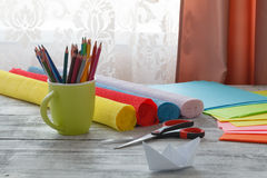 Set of origami boats and square sheets of colored paper on a woo Royalty Free Stock Photos