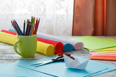 Set of origami boats and square sheets of colored paper on a woo Stock Images