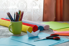 Set of origami boats and square sheets of colored paper on a woo Royalty Free Stock Photo