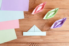 Set of origami boats and square sheets of colored paper on a wooden table Stock Photos