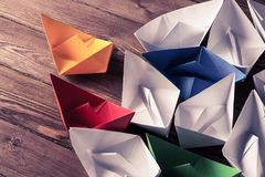 Business leadership concept with white and color paper boats on Royalty Free Stock Image