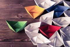 Business leadership concept with white and color paper boats on Stock Image