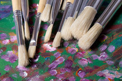 Set of paint brushes on canvas background Stock Images