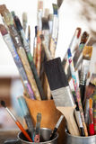 Set of paint brushes in a jar and mug Royalty Free Stock Images