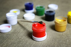 Set of paint cans. Small jars with colorful gouache paints to paint and brush royalty free stock photos