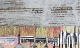 Set of paintbrushes in a wood background Stock Images