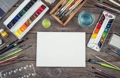 Set of painter accessories. Watercolor aquarelle paints, art brushes, palette, glass of water on old wooden background. stock image