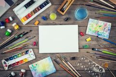 Set of painter accessories. Watercolor aquarelle paints, art brushes, palette, glass of water on old wooden background. royalty free stock image