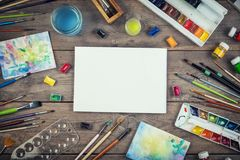 Set of painter accessories. Watercolor aquarelle paints, art brushes, palette on old wooden background. Set of painter accessories. Watercolor aquarelle paints royalty free stock images