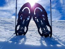 set of a pair of snowshoes or rackets of snow and two ski poles on the cold white snow ready to walk on the snowy mountain in a stock photos