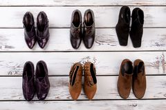 Set of pairs of women`s shoes. Wooden desks surface background Stock Photo