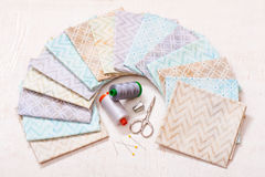 Set of pastel fabrics arranged on circle and sewing tools in center Stock Photos